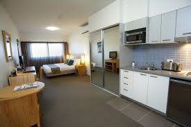 awesome efficiency apartment decorating ideas with white kitchen cabinet and gray tile backsplash also sliding mirror cool decorate a studio apartment studio furniture