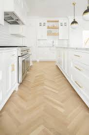herringbone wood floors with white shaker kitchen cabinets and gold brass hardware designed by the fox