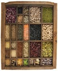 vintage wooden typesetter case drawer with variety of beans lentils peas grains and seeds isolated on white