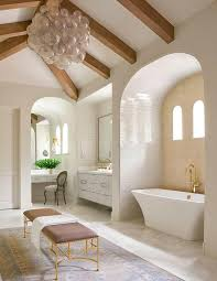 sophisticated master bathroom features a vaulted ceiling dotted with wood beams as well as a smoke gray glass bubbles chandelier oly studio muriel