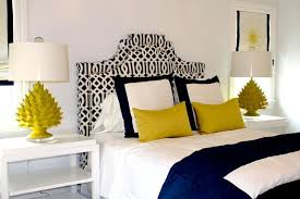 contemporary bedroom design with yellow and black accents and white wall paint color and black nightstand
