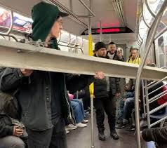 new york city subway riders help a man carry a giant construction beam onto the subway train