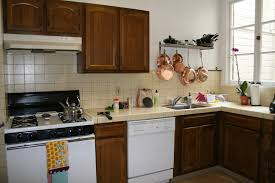 kitchen brown wooden kitchen cabinet with cream tile counter top and back splash also white
