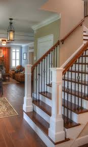 hardwood flooring up the stairs clic look rod iron baers wood railings and white posts
