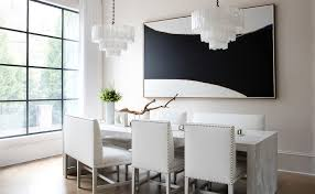 sleek modern black and white dining room boasts two white tiered capiz chandeliers hung over a marble waterfall dining table seating white leather dining