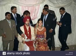 wedding guests give gifts of cash to the bride and groom at a traditional sikh wedding