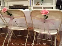 the roses and tulle decorating these chairs were purchased at a michael s a less expensive version would be to decorate chairs with kid made flowers