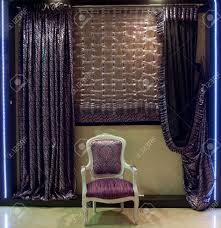 luurious old fashioned designer chair and window curtains in purple stock photo