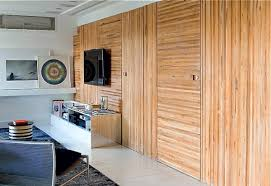Architect Flavia Gerab of Sao Paulo cleverly used panels of wood slats  turned this way and that way to disguise several doorways. The treatment  warms up the ...