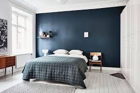 Scandinavian bedroom with dark blue wall