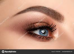 close up of blue woman eye with beautiful brown with red and orange shades smokey eyes makeup modern fashion make up