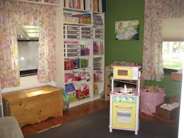 white ikea toy storage filled with children goods matched with green wall  plus floral curtains for