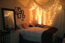 teenage girl bedroom design with hanging white canopy bed curtains with string le lights over corner bed decoration plus white wood bedside table with