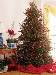 a large Christmas tree with hot red ornaments and with red gifts
