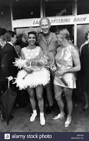 Teddy Tinling mit Lea Pericoli tragen ihren Strauß gefiederten Schöpfung  und Ann Jones mit ihrem Gold Lame Kleid verziert mit blauen Blumen Muster,  Gold Schuhe und echtem gold Tennisschläger. Juni 1968 P012373