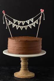 clic birthday cake on a marble cake stand with a wooden base