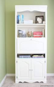 a white clay painted bookshelf with colorful books awisconsin sign and a gold decorative sphere