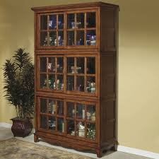 tall mahogany wooden bookcase with three pair of sliding glass doors having pretty mouldings on white tile flooring
