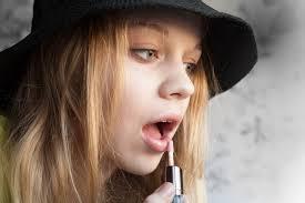 applying pink lipstick