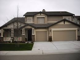 modern home exterior paint using latte color on the walls and dark gray on roof tiles