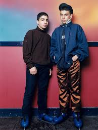 Two <b>young boys</b> leaning against wall looking directly at camera ...