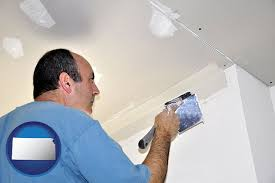 a contractor spackling drywall with kansas icon