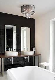 a ceiling light with crystal accents and a drum shade in a bathroom