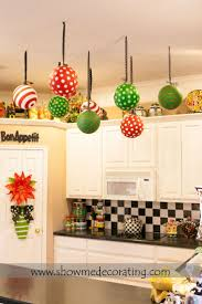 Christmas decor. Oversized Christmas ornaments tied with coordinating  ribbon suspending from the ceiling leaves the
