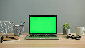 green office desk. view of laptop with green screen on the office table. chroma key. close up desk