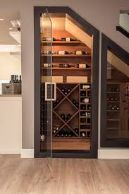 a small yet stylish wine cellar under the stairs with various plywood shelves for the bottles