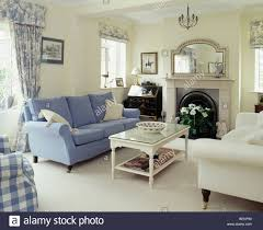 Blue and cream sofas on either side of fireplace in cream living room with  cream carpet and white glass-topped coffee-table