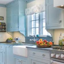 white farmhouse near window between blue kitchen cabinets plus nice dry and cake plate