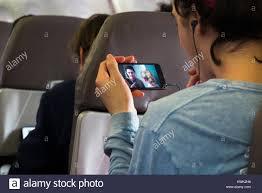 Passeggero maschio giocando un visualizza filmato, film o programma  televisivo sul suo telefono cellulare - attiva la modalità di uso in aereo,  su Embraer aereo / aeroplano / Aereo Foto stock - Alamy