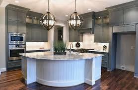 kitchen with gray cabinets white island with white subway tile backsplash and globe pendant lights