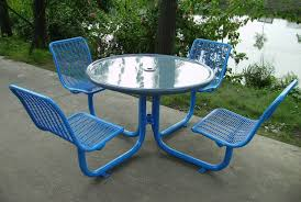 glass top round riverside park picnic table with metal base and attached chair seats painted with blue color on exposed concrete floor tiles ideas