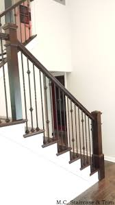 Removal of carpet, wooden railing and wooden balusters. Installation of  stained treads, risers, box newels, handrail, square rosettes and iron  balusters.