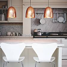 kitchen with white range cooker breakfast bar and copper pendant lights