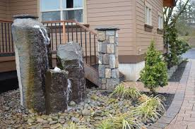 plant bed with rocks and cascading water feature over natural stone columns