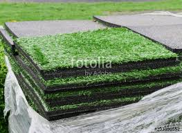 stacks of artificial turf grass rug tiles with rubber under layer for indoor outdoor landscaping