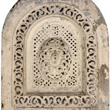 wonderful antique cast iron arched fireplace cover dating from the early 1900 s it features a large oval medallion design in the center surrounded by a