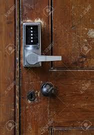 simple door handle electronic lock with numeric ons on old wooden door stock photo 61157363