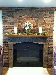 faux stone wall panels for fireplace design wiith brown color and fireplace with glass and wood screen plus flower decor and candle stand above fireplace