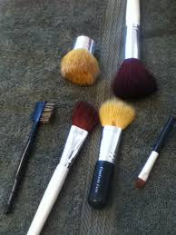makeup brushes after they have been cleaned in a mason jar with marbles