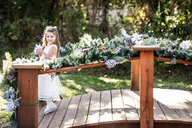 a cute shot of the flower walking over a rustic wooden bridge at bakers ranch during amber and jackson s wedding celebrations