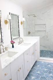 white and gold bathroom features a white dual washstand adorned with brass pulls paired with honed white marble fitted with his and hers sinks and gooseneck