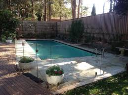 frameless glass pool fence with aluminium spigots into tiles and shaped around corner