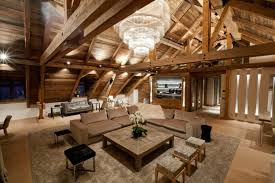 modern rustic apartment with visible wooden support incredible crystal chandelier installed on iced winter home