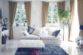living room with blue area rug white couch and curtained windows