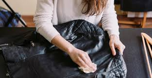 brunette cleaning a black leather jacket with a towel
