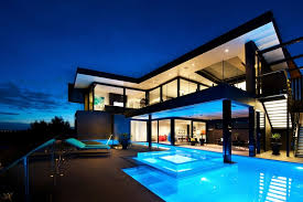 Black home with blue lit swimming pool